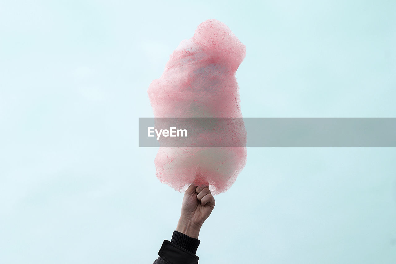 Low Angle View Of Hand Holding Cotton Candy Against Clear Sky