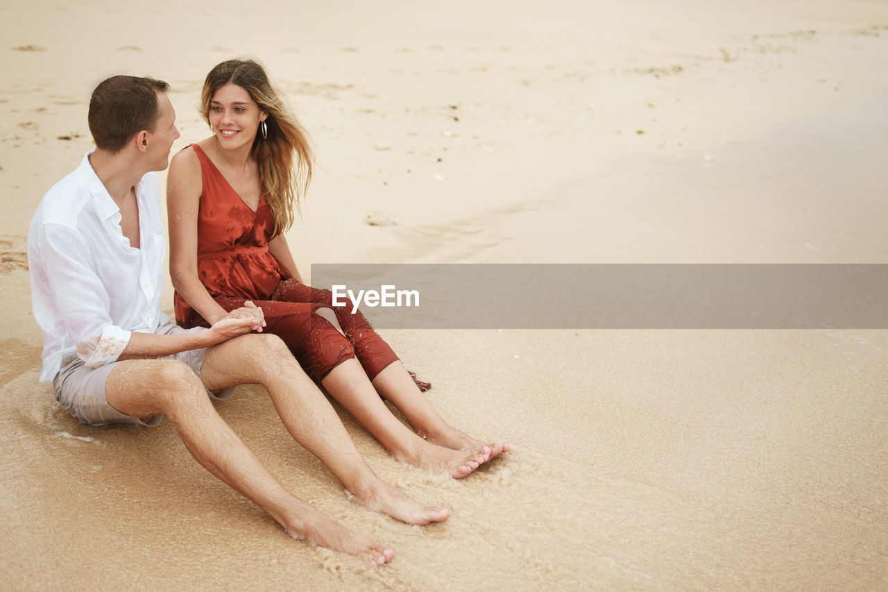 Young couple sitting on sand at beach