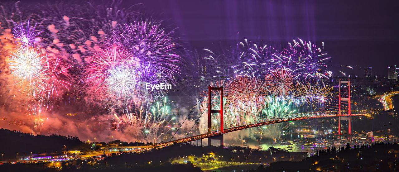 Panoramic view of illuminated bosphorus bridge with firework display at night
