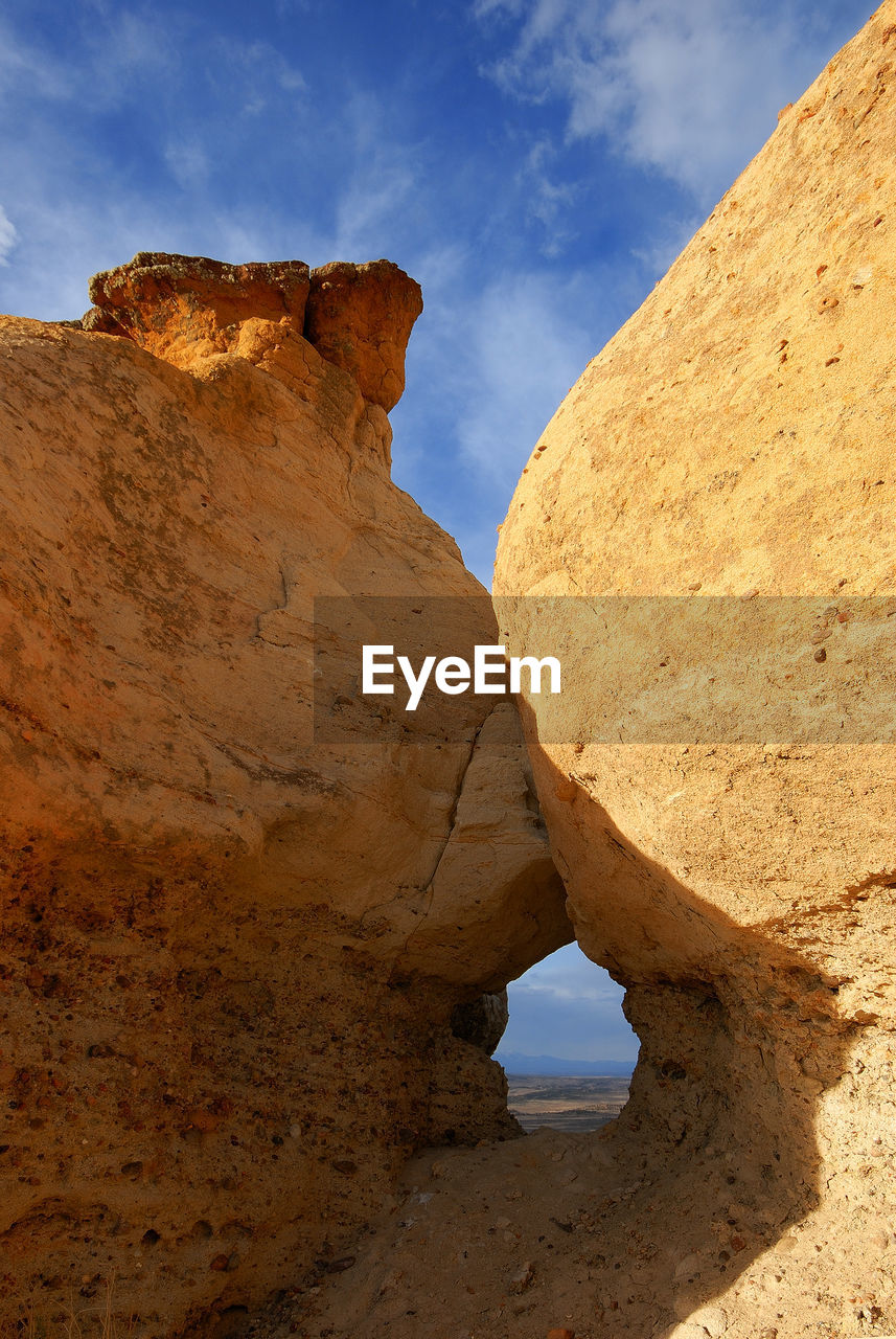 rock formation, rock - object, geology, physical geography, sky, nature, beauty in nature, tranquility, day, outdoors, scenics, tranquil scene, travel destinations, natural arch, low angle view, no people, arid climate, cliff, landscape