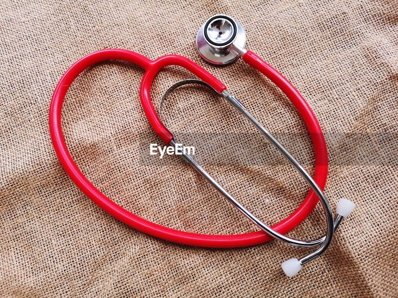 stethoscope, medical instrument, medical supplies, medical equipment, still life, healthcare and medicine, high angle view, indoors, no people, close-up, diagnostic medical tool, red, textile, equipment, medical exam, listening, single object, studio shot, pulse trace, personal accessory