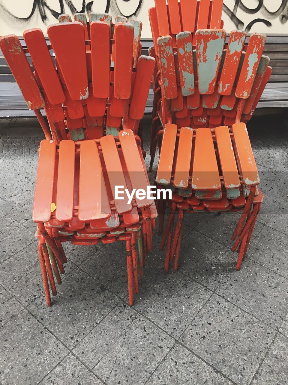 High angle view of orange stacked chairs on footpath
