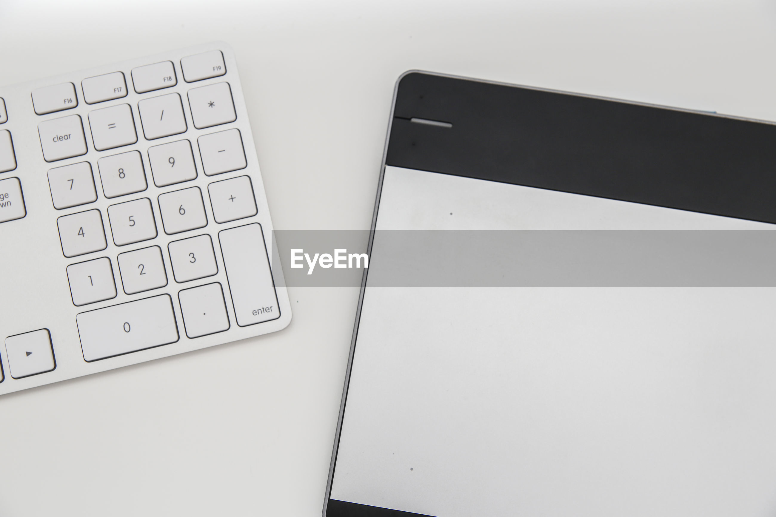High angle view of computer keyboard and laptop on white background