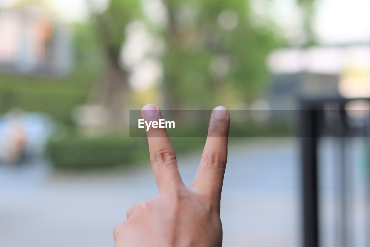 human hand, human body part, hand, body part, finger, human finger, one person, focus on foreground, gesturing, real people, unrecognizable person, lifestyles, day, showing, leisure activity, close-up, hand sign, personal perspective, selective focus, outdoors, human limb