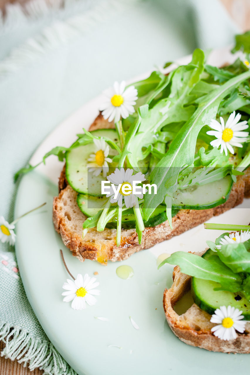 Fresh Edible Flowers And Vegetables Garnished On Bread