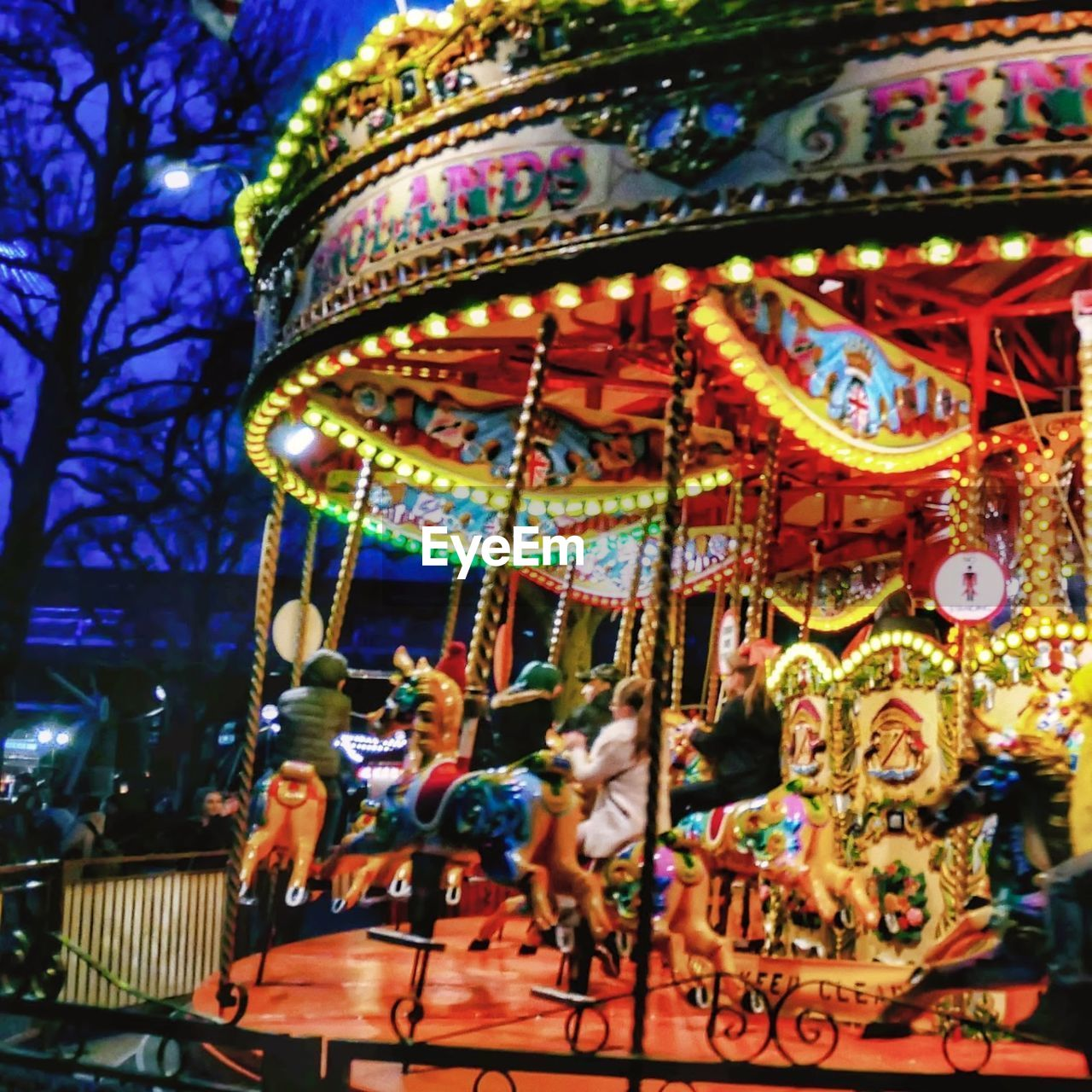 amusement park, amusement park ride, arts culture and entertainment, carousel, illuminated, representation, multi colored, enjoyment, animal representation, leisure activity, group of people, outdoors, night, carousel horses, real people, fun, built structure, architecture, art and craft, merry-go-round