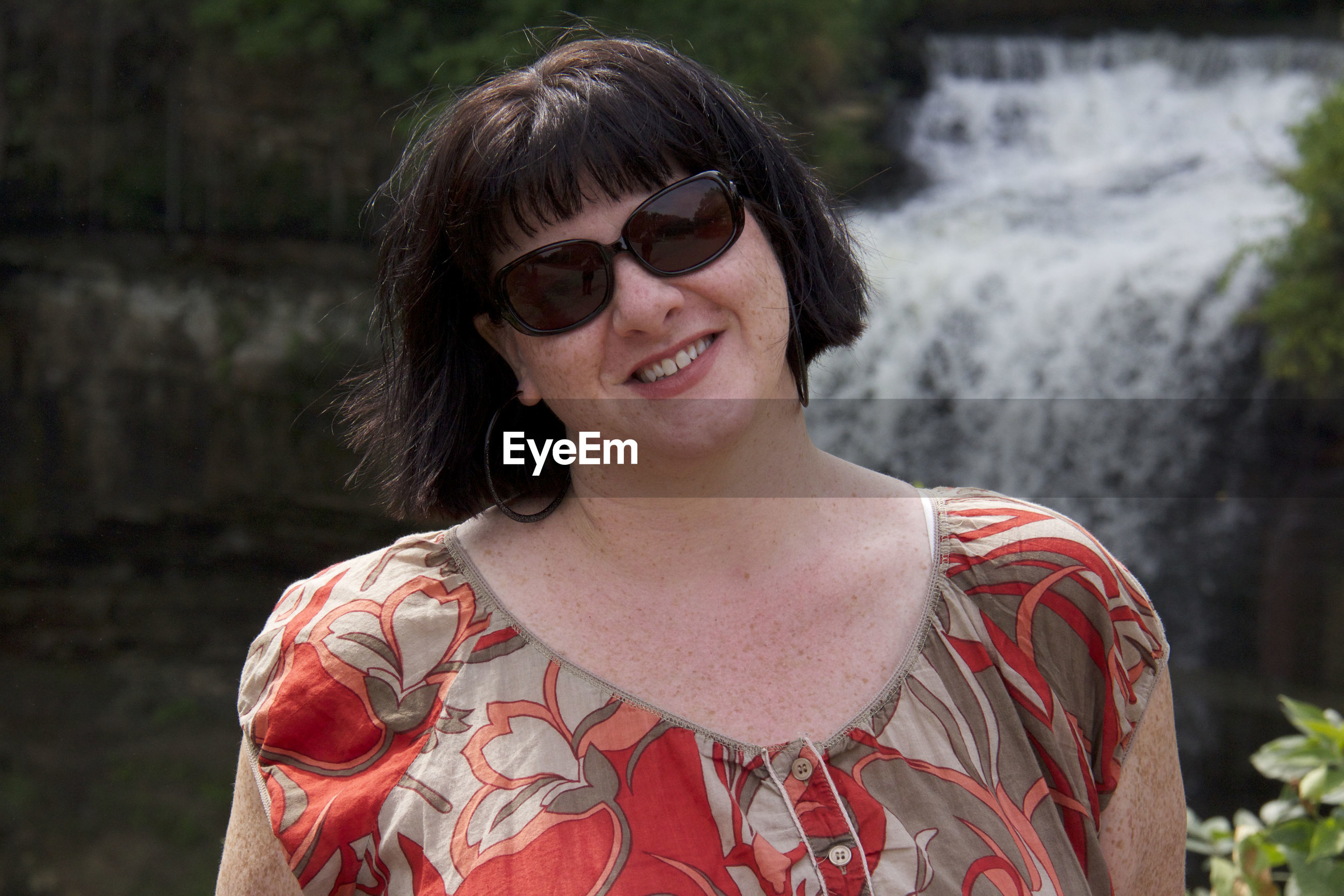 Portrait of smiling overweight woman wearing sunglasses against waterfall