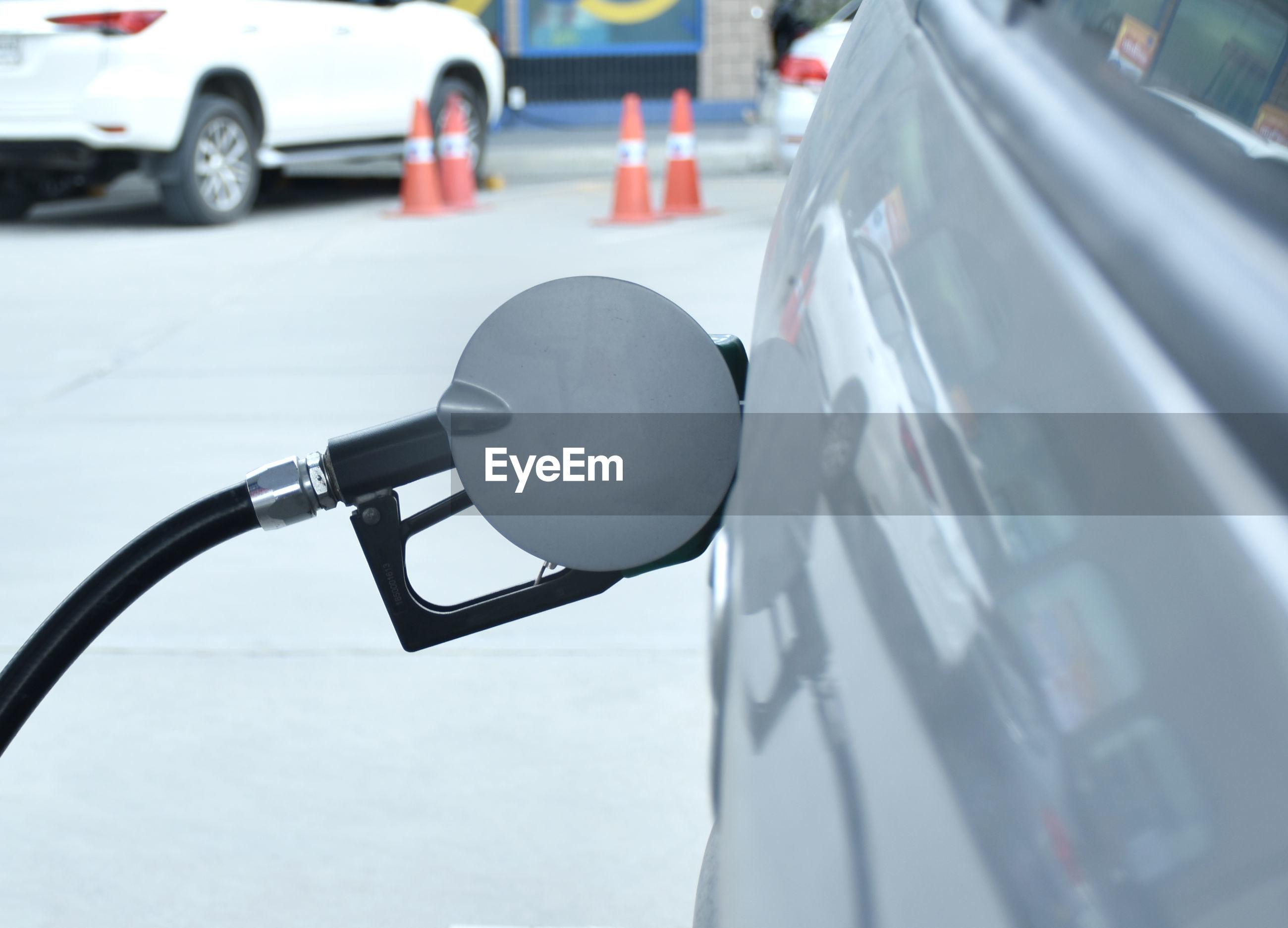 Filling gasoline fuel in car holding nozzle. refilling oil for transportation or travel.