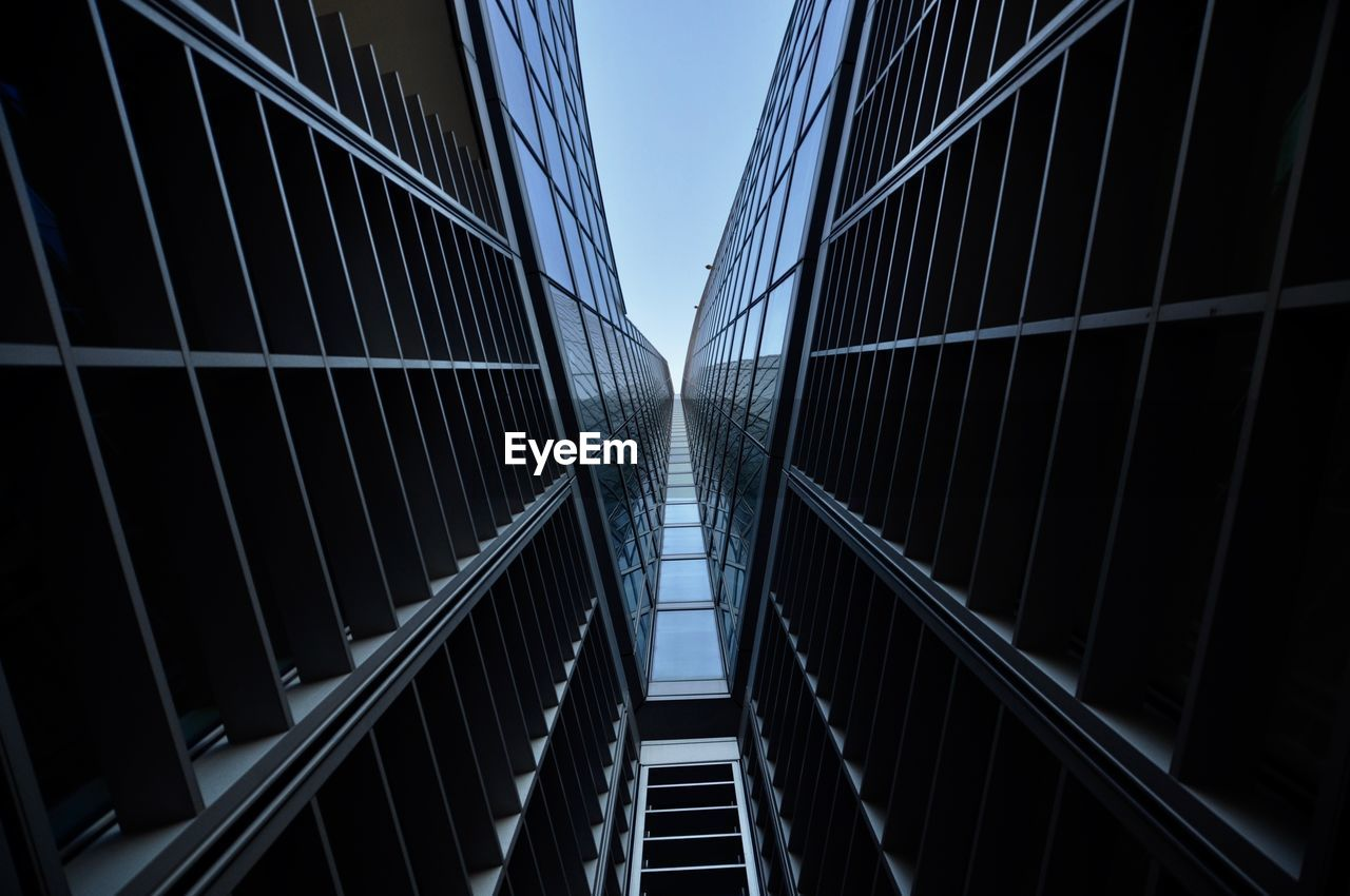 built structure, architecture, no people, low angle view, building exterior, bridge, building, sky, clear sky, nature, outdoors, railing, connection, modern, footbridge, city, day, bridge - man made structure, glass - material, office building exterior, skyscraper