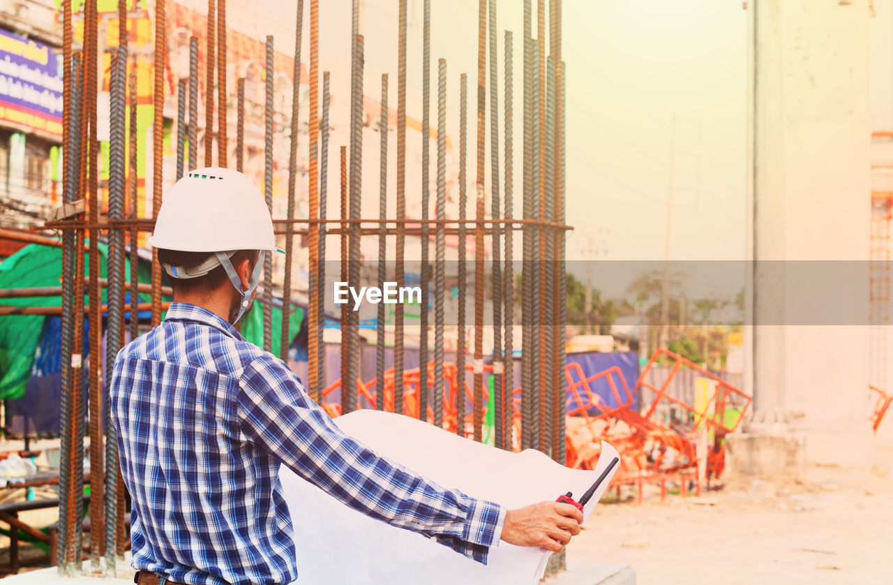real people, one person, wireless technology, working, men, communication, construction site, construction industry, standing, architecture, males, technology, built structure, holding, waist up, lifestyles, casual clothing, focus on foreground, occupation, outdoors