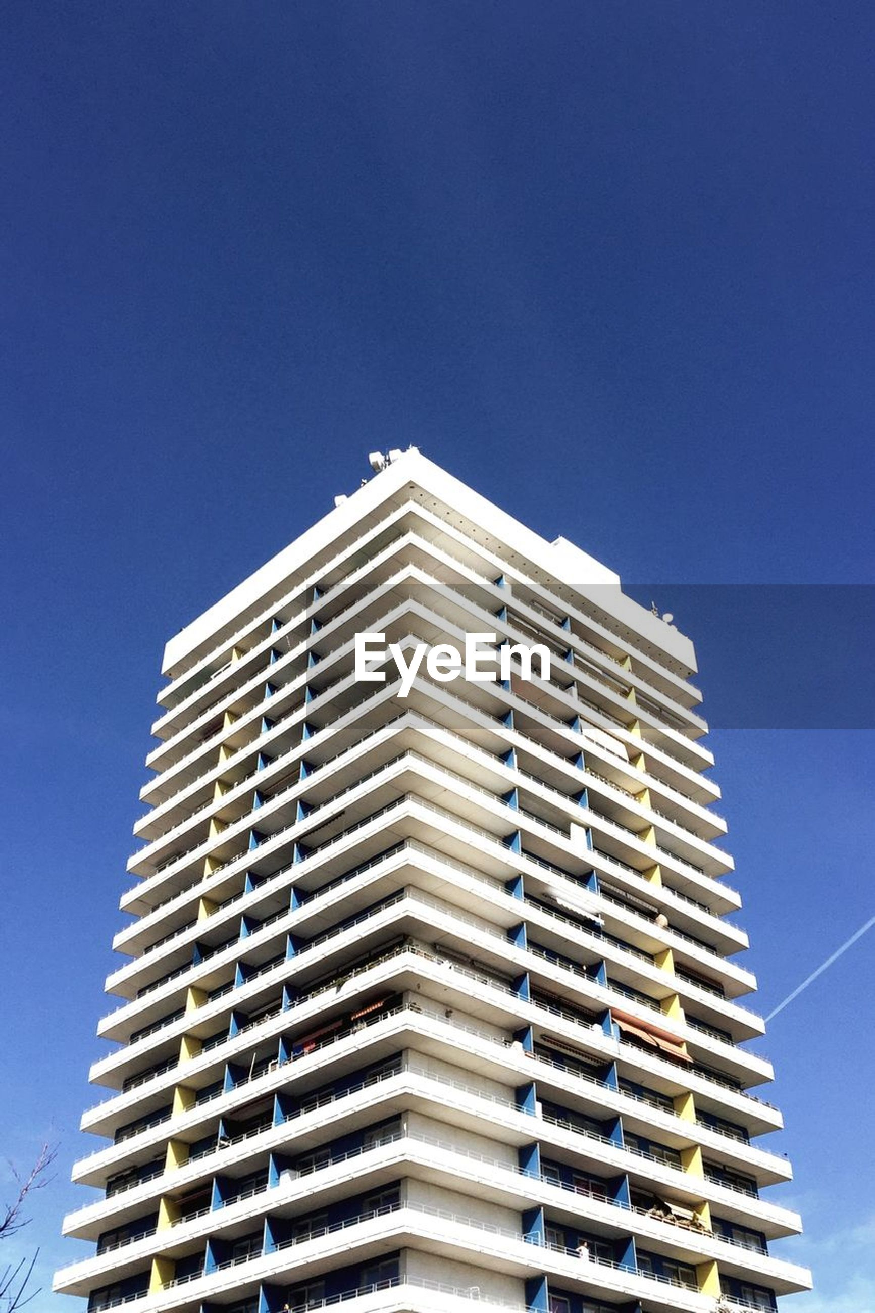 low angle view, building exterior, architecture, built structure, clear sky, no people, outdoors, day, window, sunlight, blue, sky, apartment, city