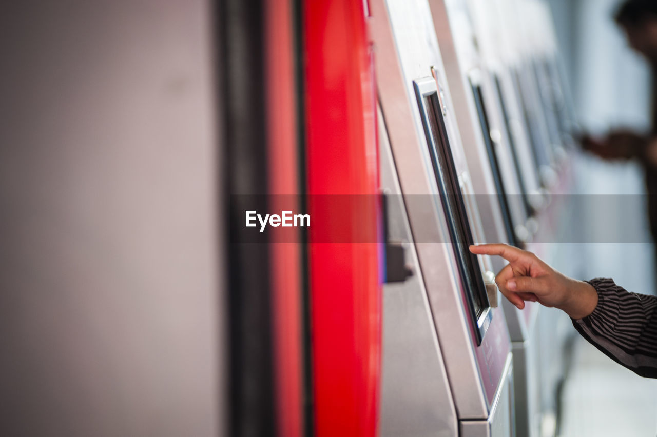 Cropped hand using kiosk at subway station