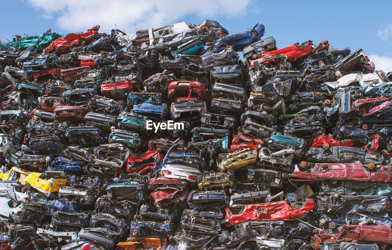 large group of objects, abundance, sky, stack, day, no people, junkyard, environmental issues, garbage, outdoors, recycling, heap, nature, pollution, cloud - sky, environment, environmental damage, metal, scrap metal, still life, recycling center