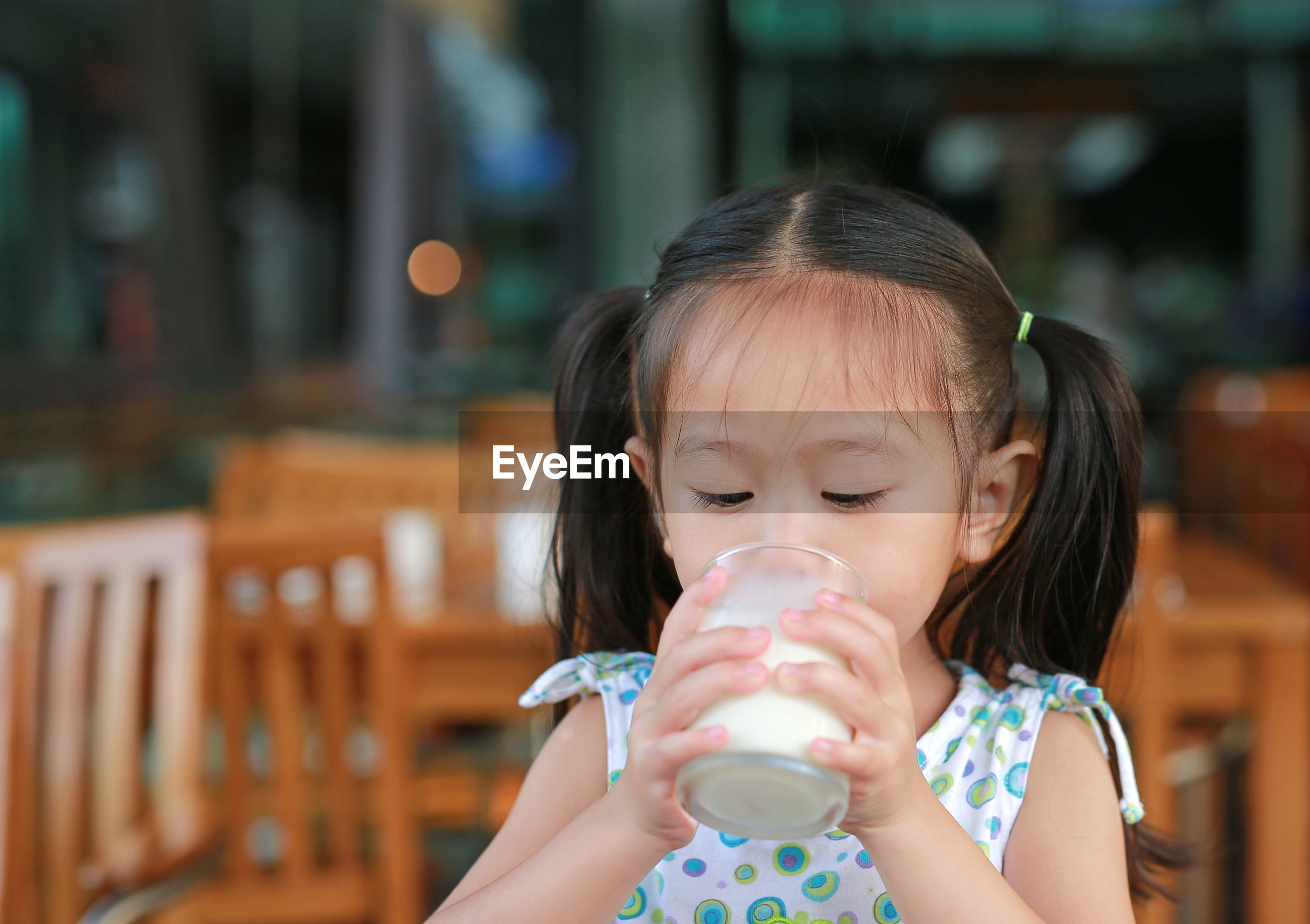 Girl drinking milk from glass at cafe