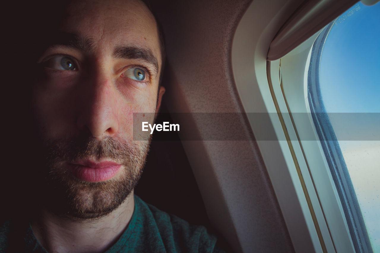 Thoughtful man looking through window in airplane