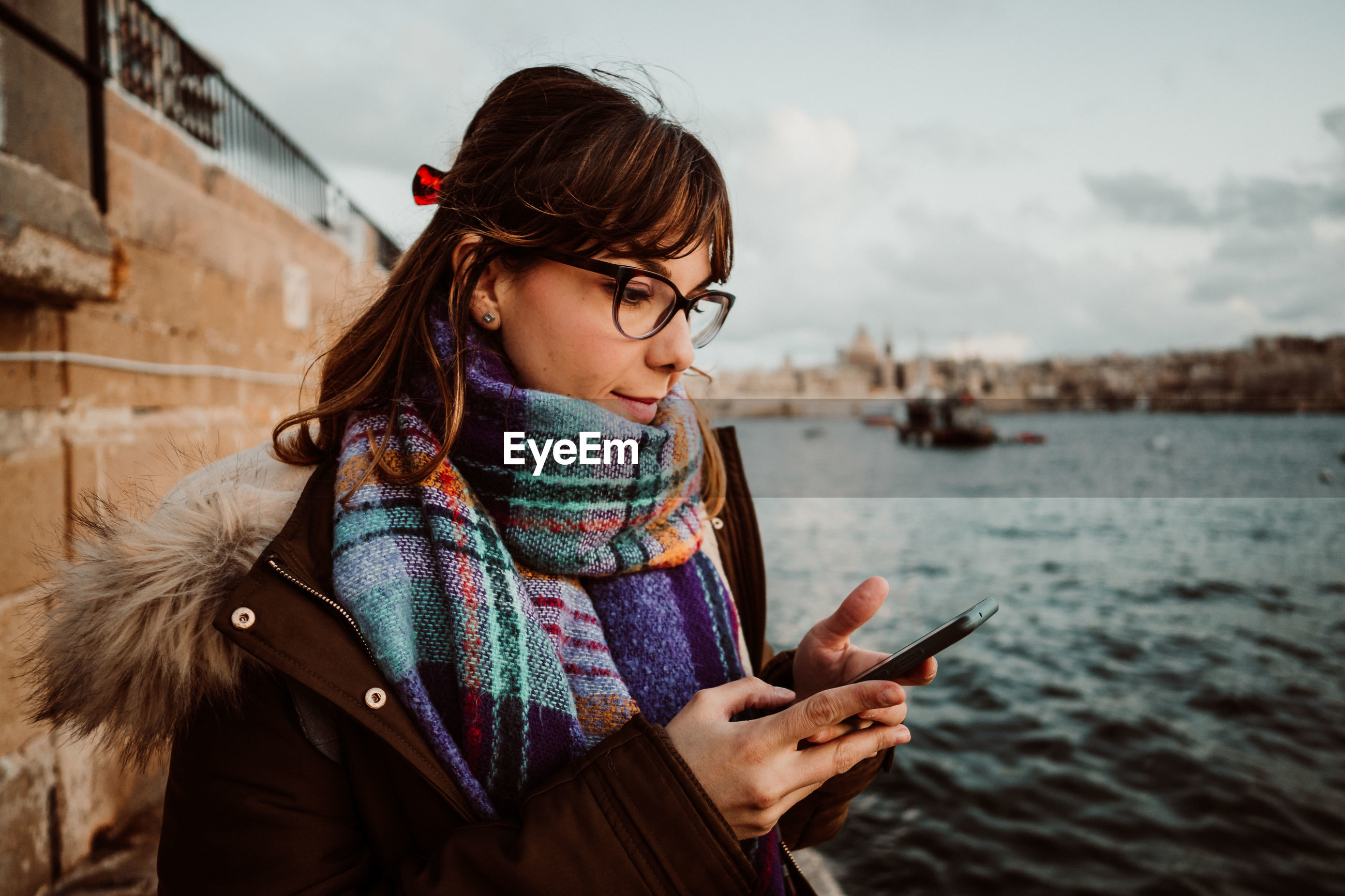 Close-up of woman wearing eyeglasses using smart phone standing by sea