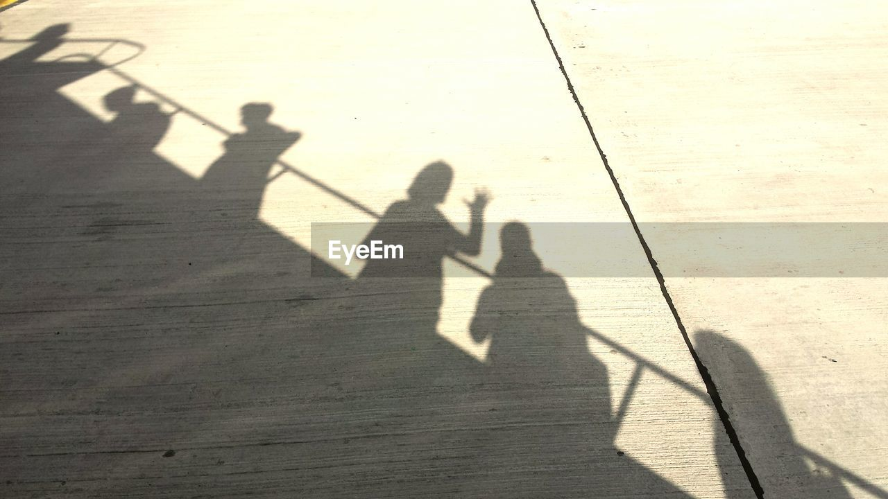 LOW SECTION OF PEOPLE STANDING BY SHADOW ON THE GROUND