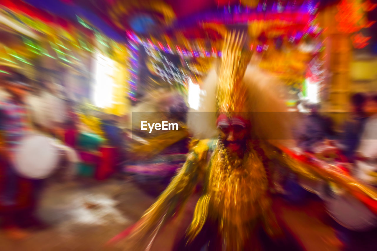 blurred motion, night, motion, arts culture and entertainment, costume, speed, multi colored, long exposure, real people, illuminated, celebration, fun, outdoors, lifestyles, leisure activity, carnival, dancing, traditional festival, enjoyment, men, traditional dancing, carousel, people