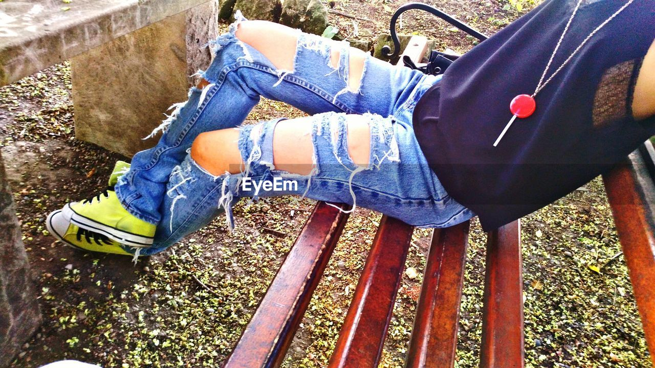 low section, one person, real people, day, human leg, casual clothing, shoe, outdoors, leisure activity, sitting, lifestyles, young adult, people