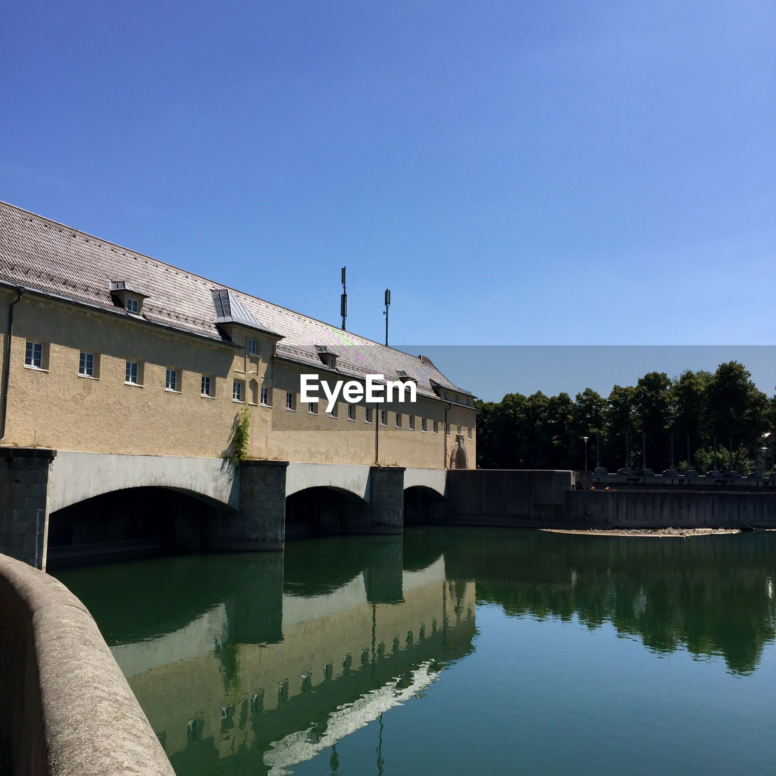 Exterior of building over river against clear blue sky
