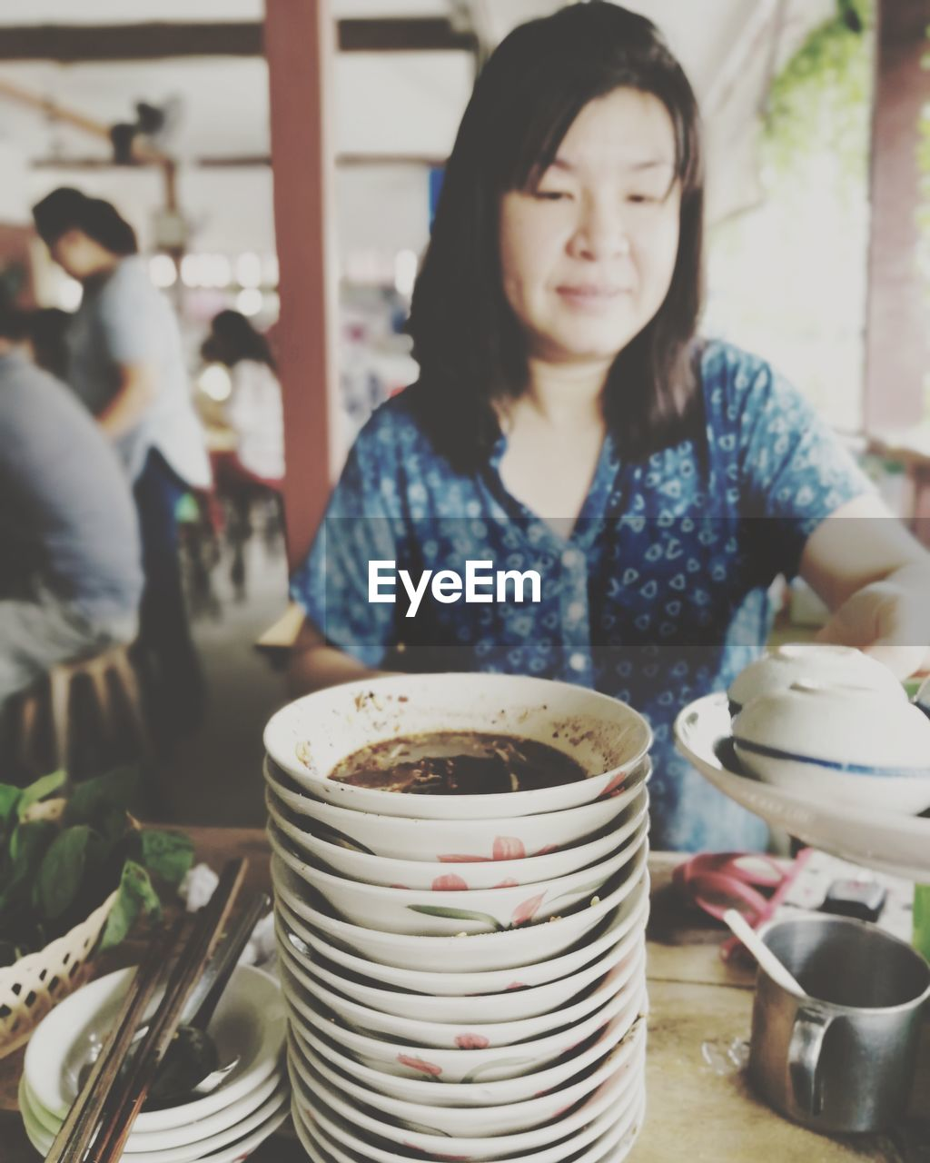 one person, food and drink, real people, indoors, cup, holding, front view, drink, focus on foreground, lifestyles, women, waist up, food, table, casual clothing, bowl, coffee cup, kitchen utensil