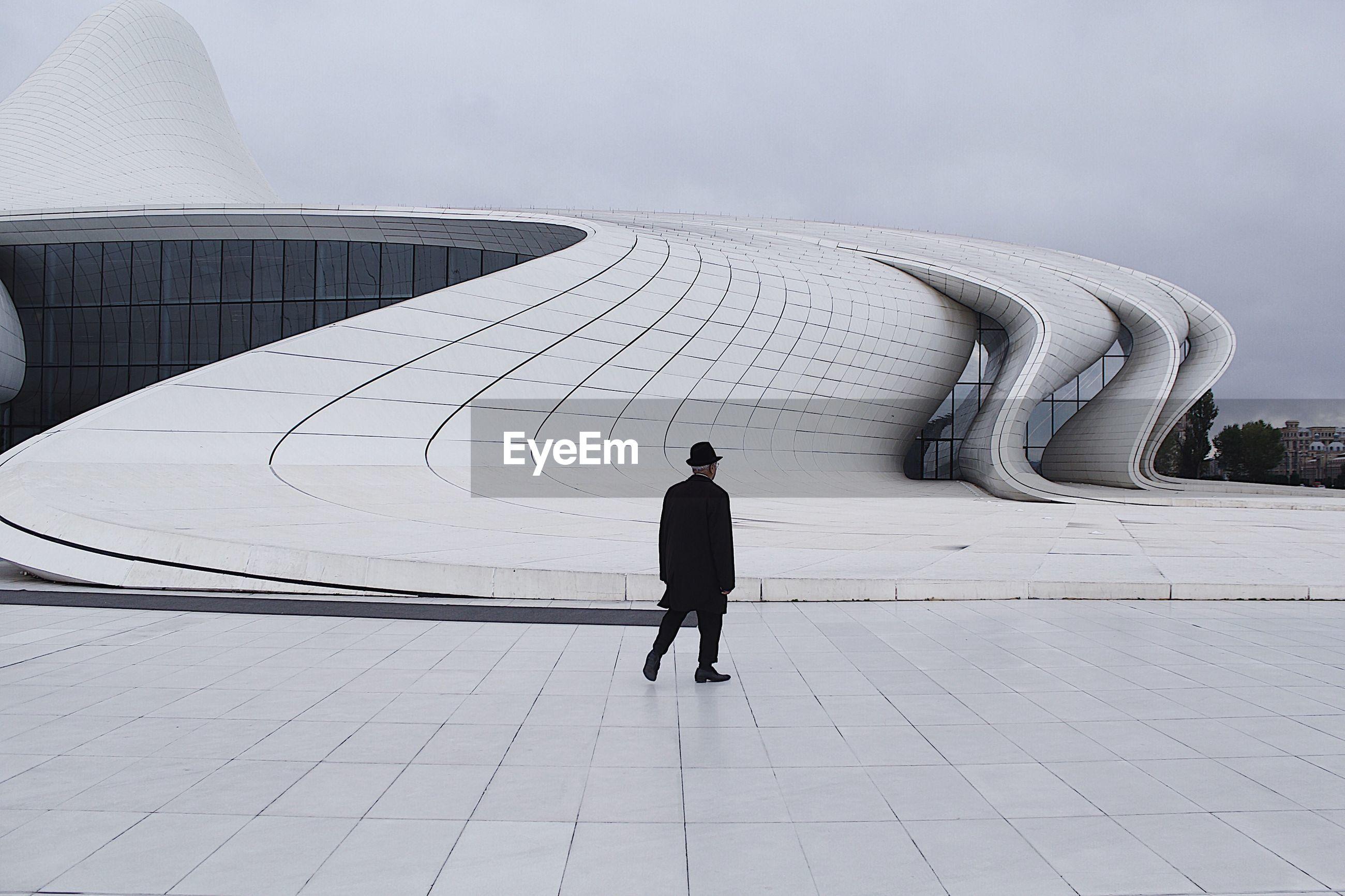 Rear view of man walking outside heydar aliyev center museum