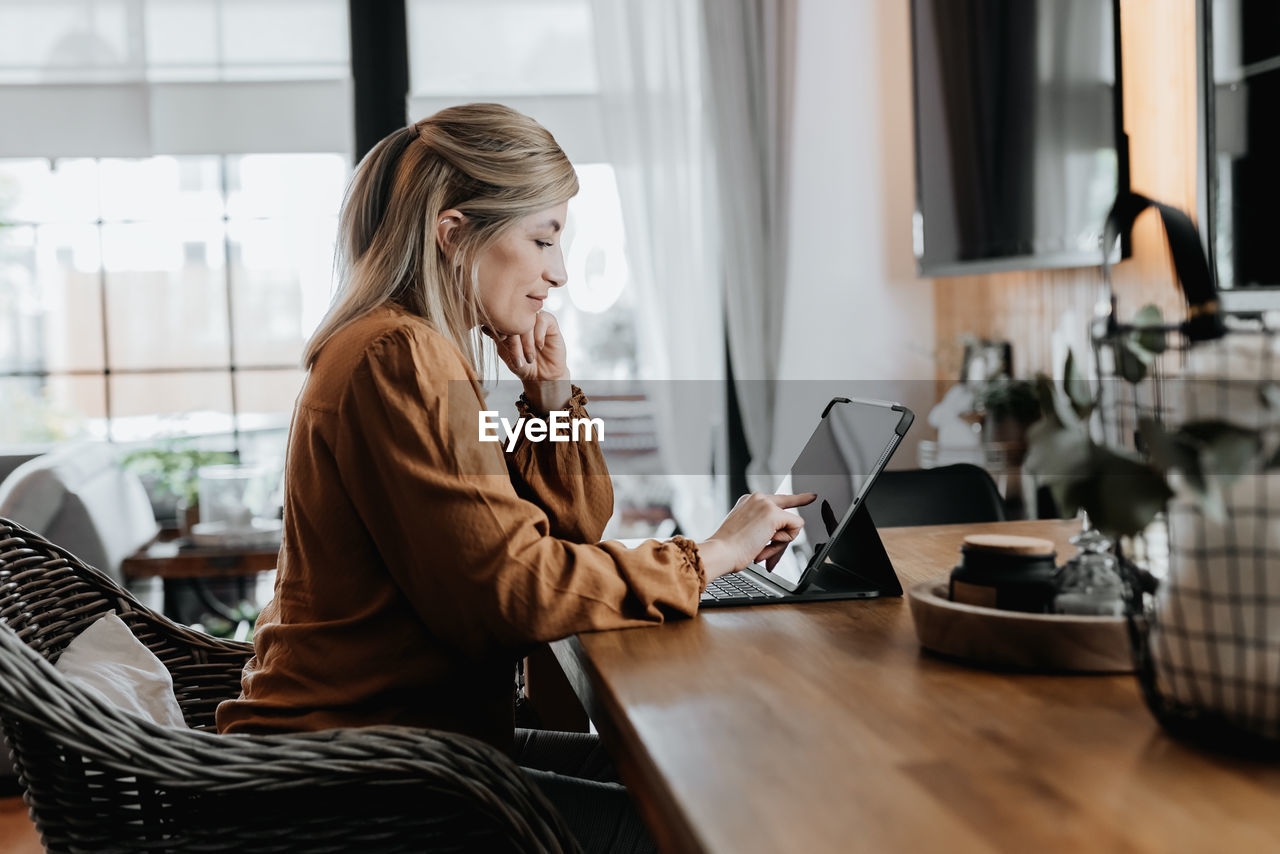 Side view of businesswoman talking on phone at home