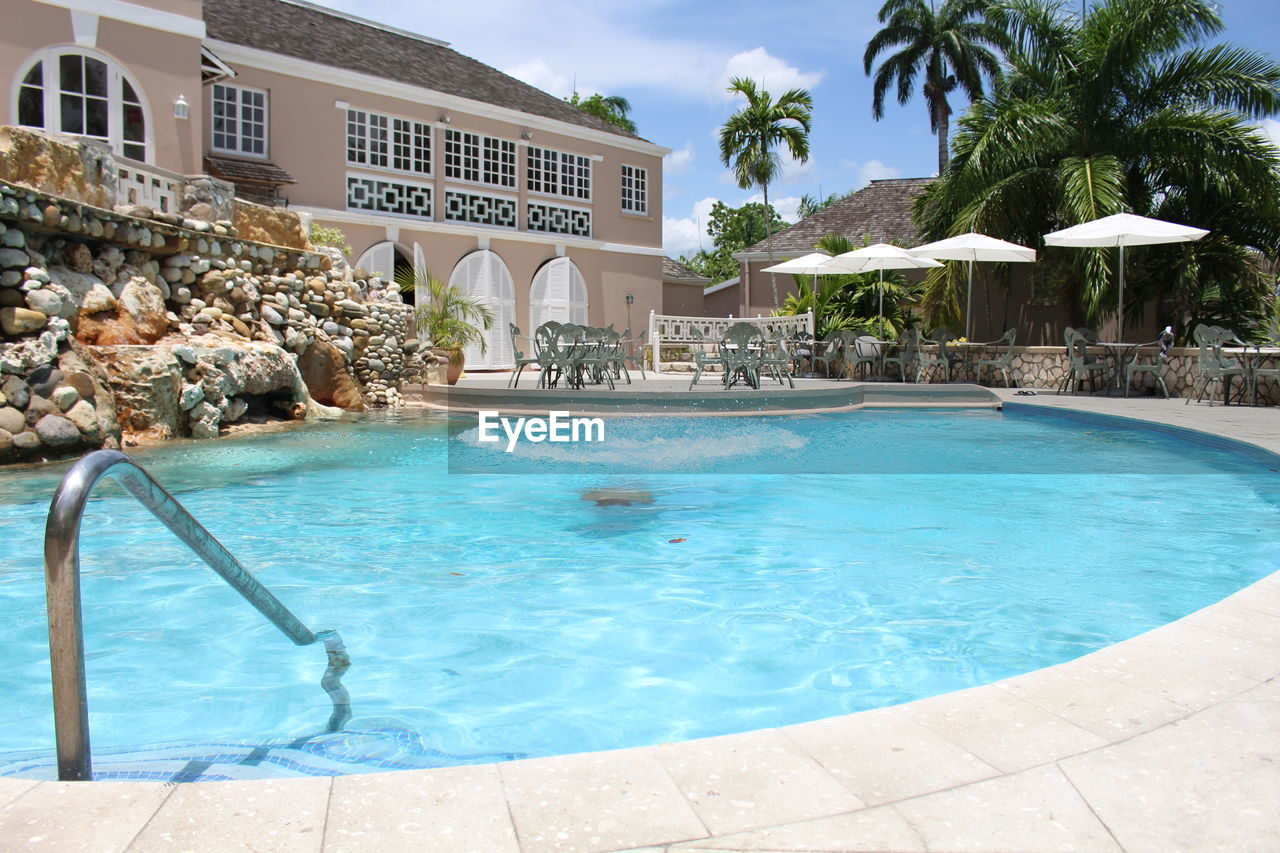 swimming pool, water, poolside, tourist resort, palm tree, architecture, swimming, luxury, luxury hotel, day, vacations, summer, outdoors, blue, no people, tree, nature, sky