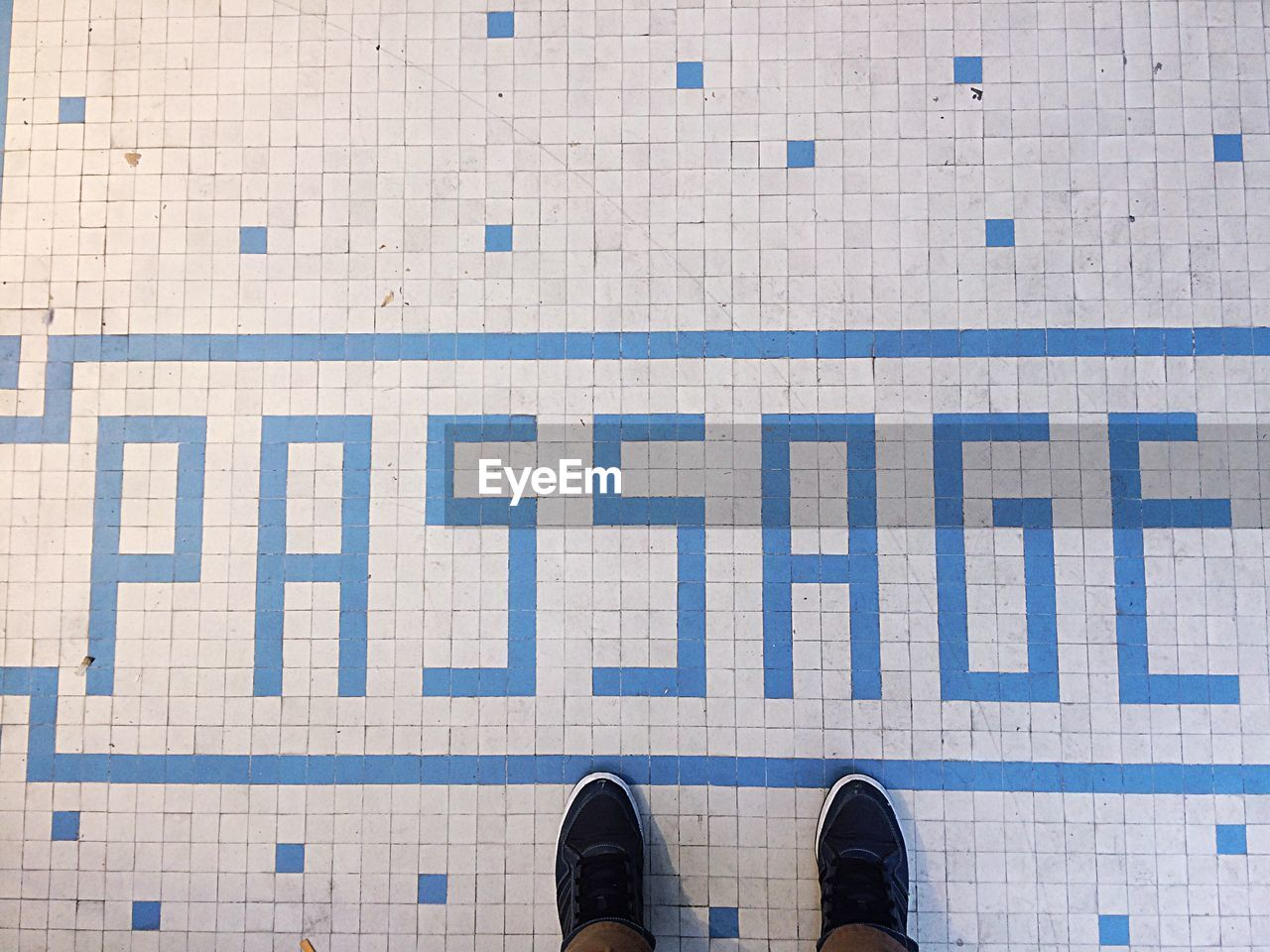 Low section of man standing by text on tiled floor