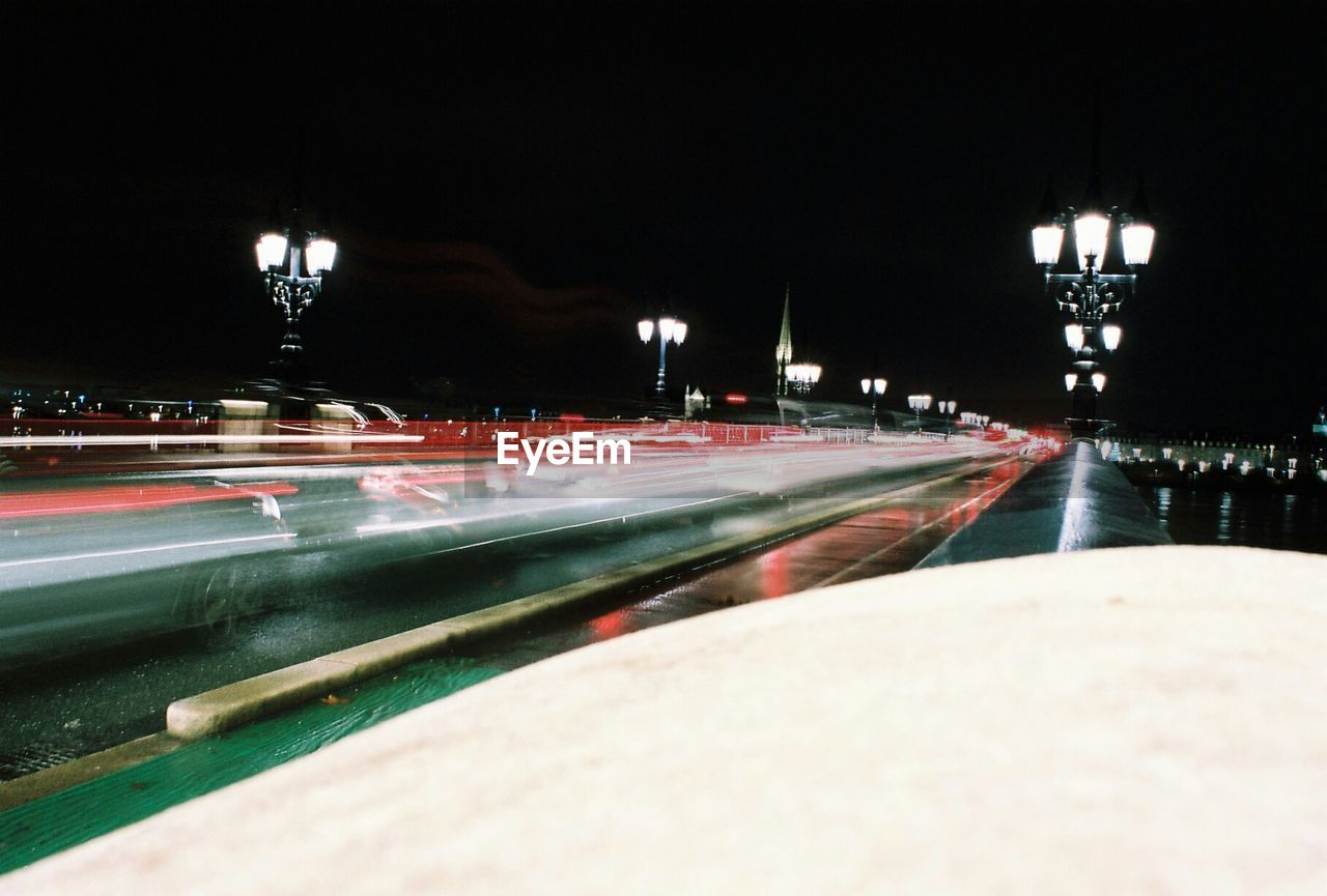 View Of Light Trails On Street Along Lamp Posts