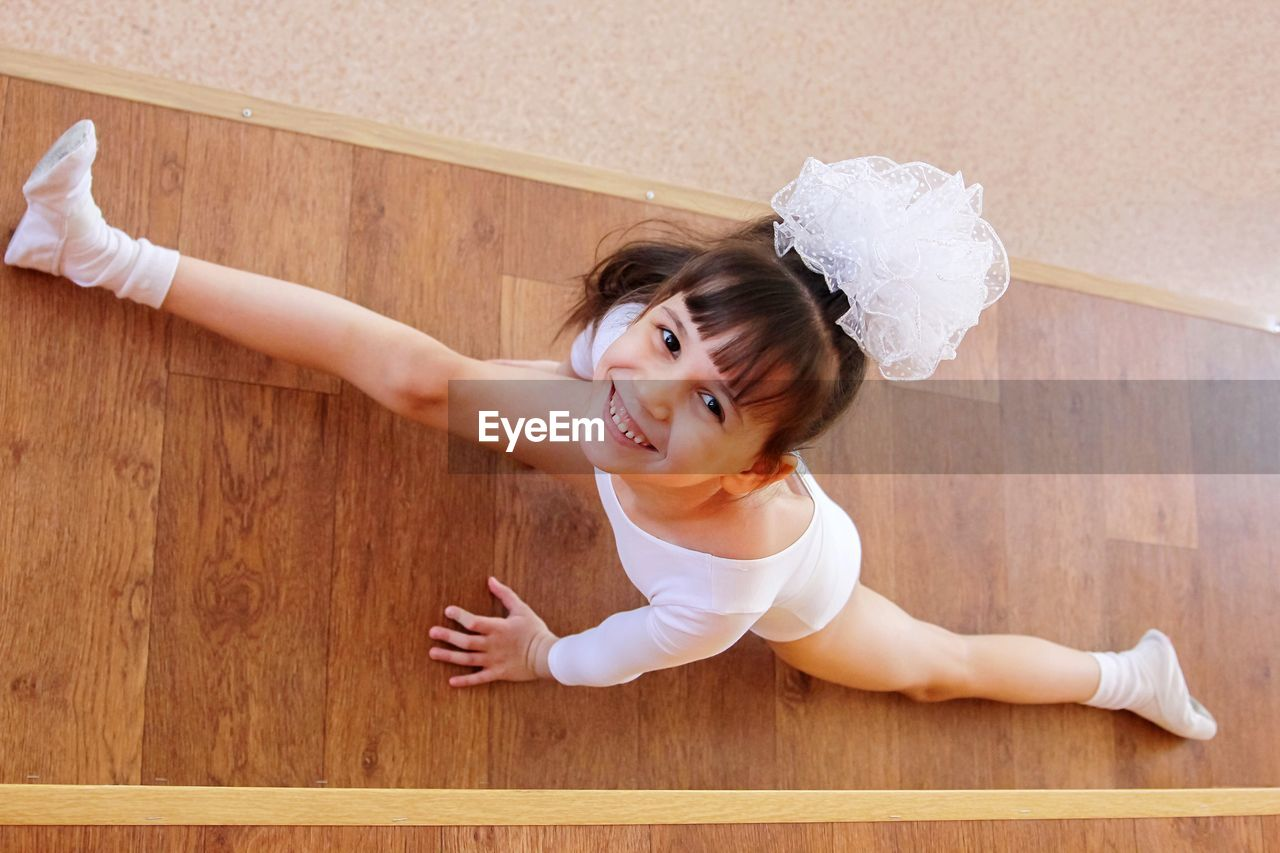 High angle portrait of cute girl stretching on hardwood floor