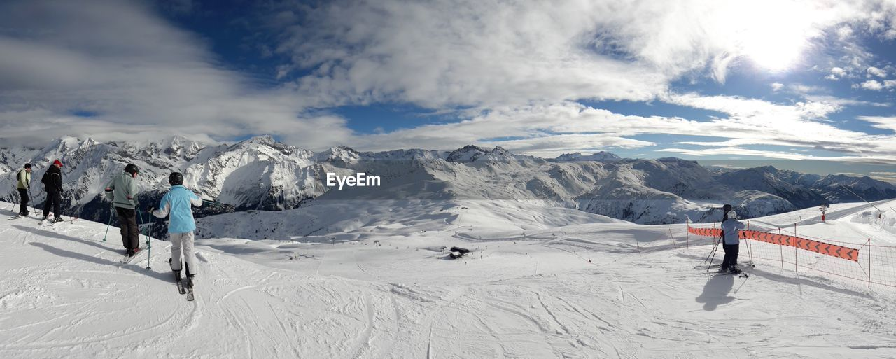 winter, cold temperature, snow, sky, real people, scenics - nature, sport, mountain, beauty in nature, cloud - sky, white color, leisure activity, nature, winter sport, day, non-urban scene, mountain range, lifestyles, adventure, snowcapped mountain, warm clothing