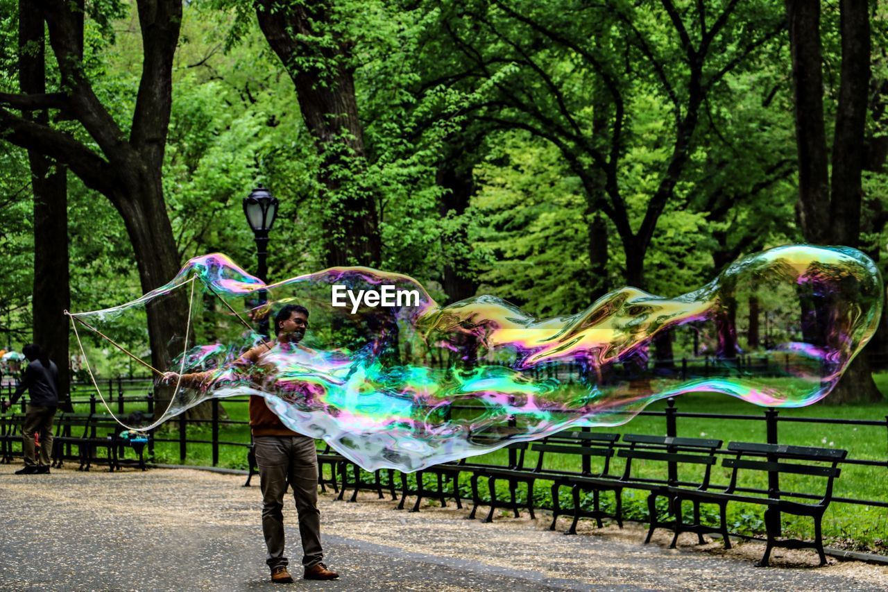 tree, plant, multi colored, nature, one person, bubble, real people, day, park, leisure activity, full length, growth, standing, young adult, park - man made space, creativity, outdoors, fun, lifestyles