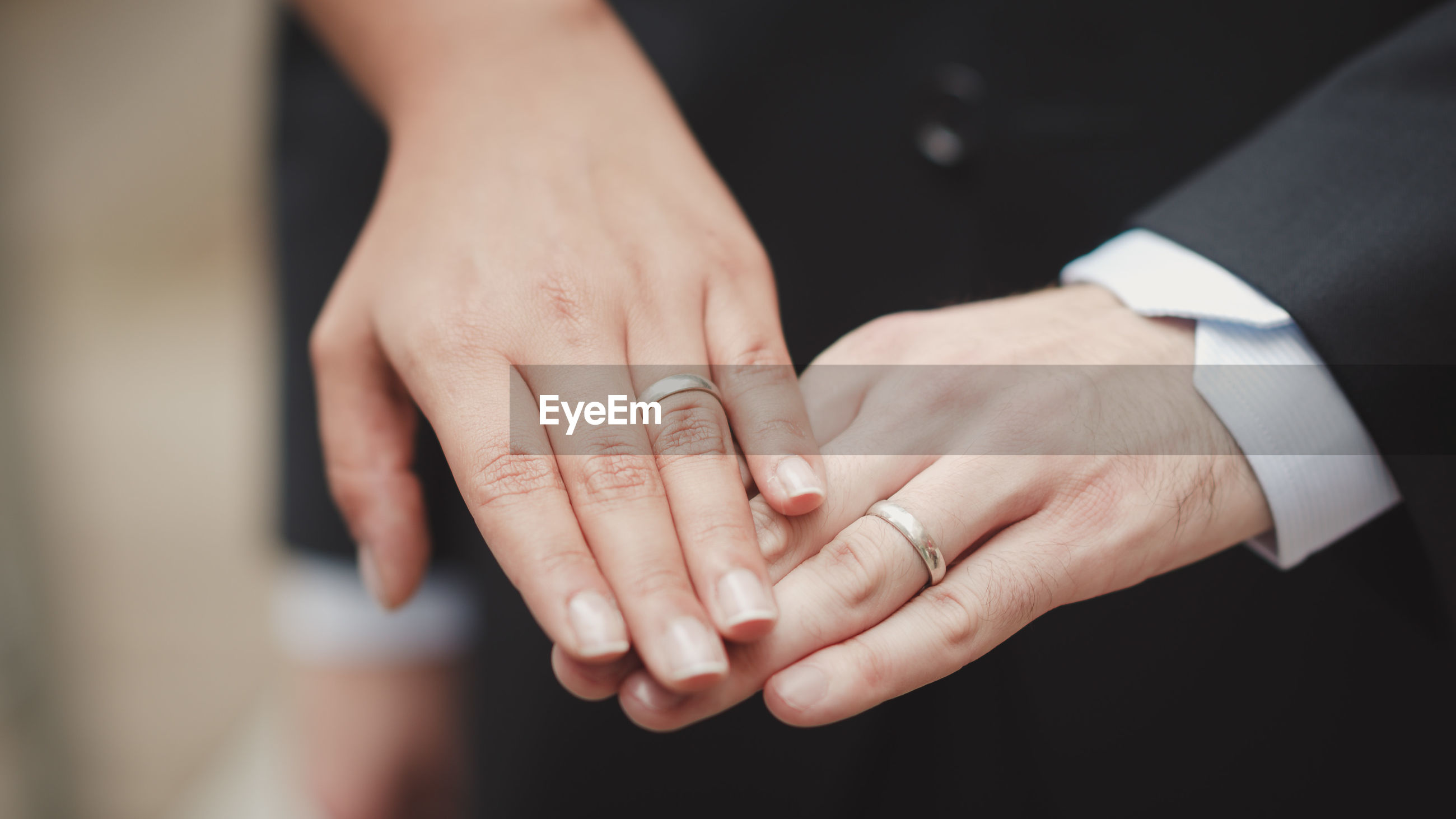 Midsection of couple showing wedding rings