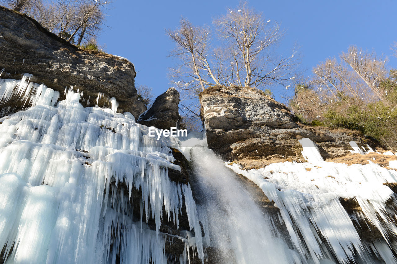 beauty in nature, cold temperature, winter, sky, nature, tree, snow, rock, scenics - nature, rock - object, no people, day, environment, waterfall, rock formation, tranquility, solid, plant, land, outdoors, flowing water, flowing, icicle, formation