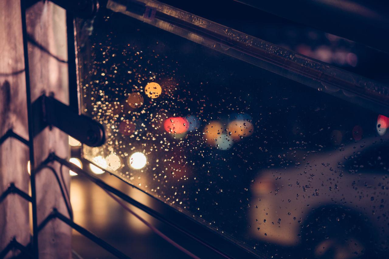 Close-Up Of Wet Glass Window During Rainy Season At Night