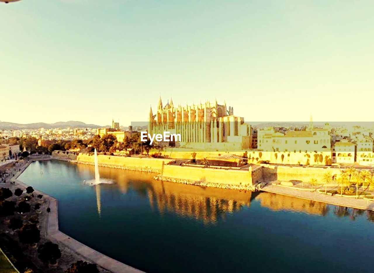 architecture, built structure, building exterior, clear sky, water, history, reflection, no people, travel destinations, sky, outdoors, day, city, cityscape, nature, ancient civilization