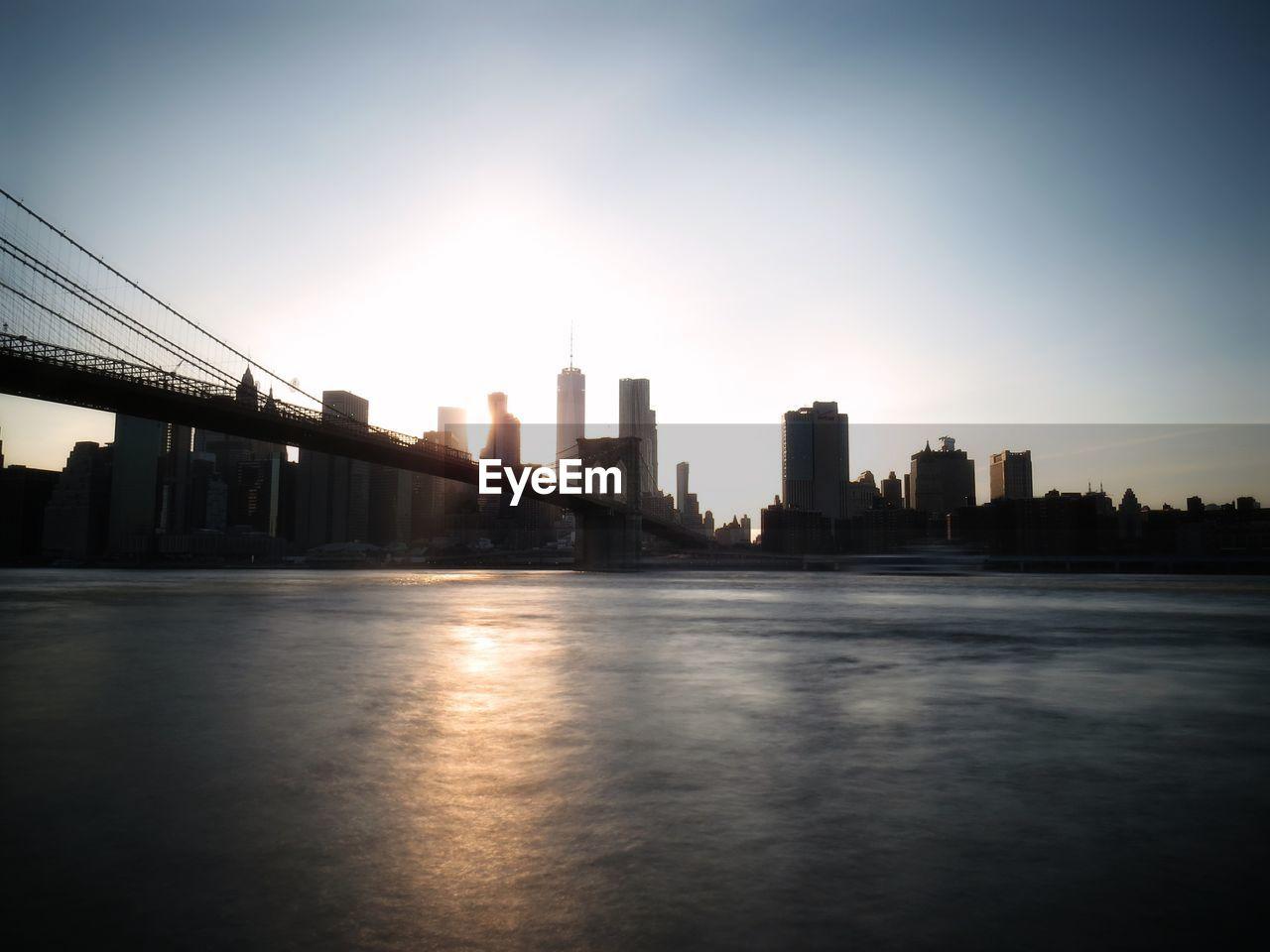 Brooklyn Bridge With Silhouette Buildings In City Against Sky