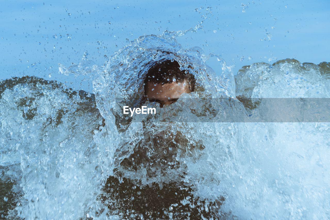 Young man swimming in splashing sea
