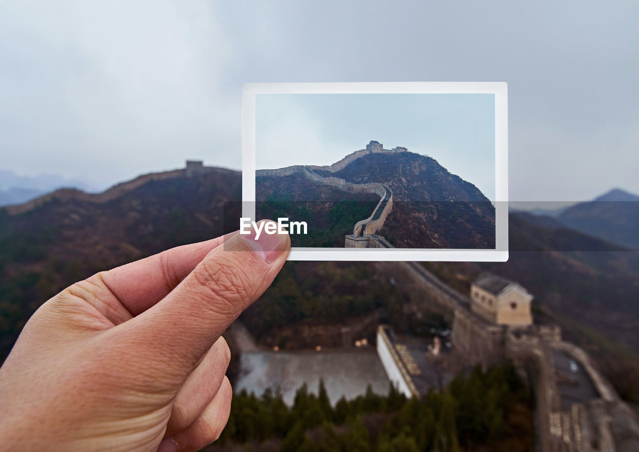 Close-Up Of Hand Holding Photograph Against Mountain