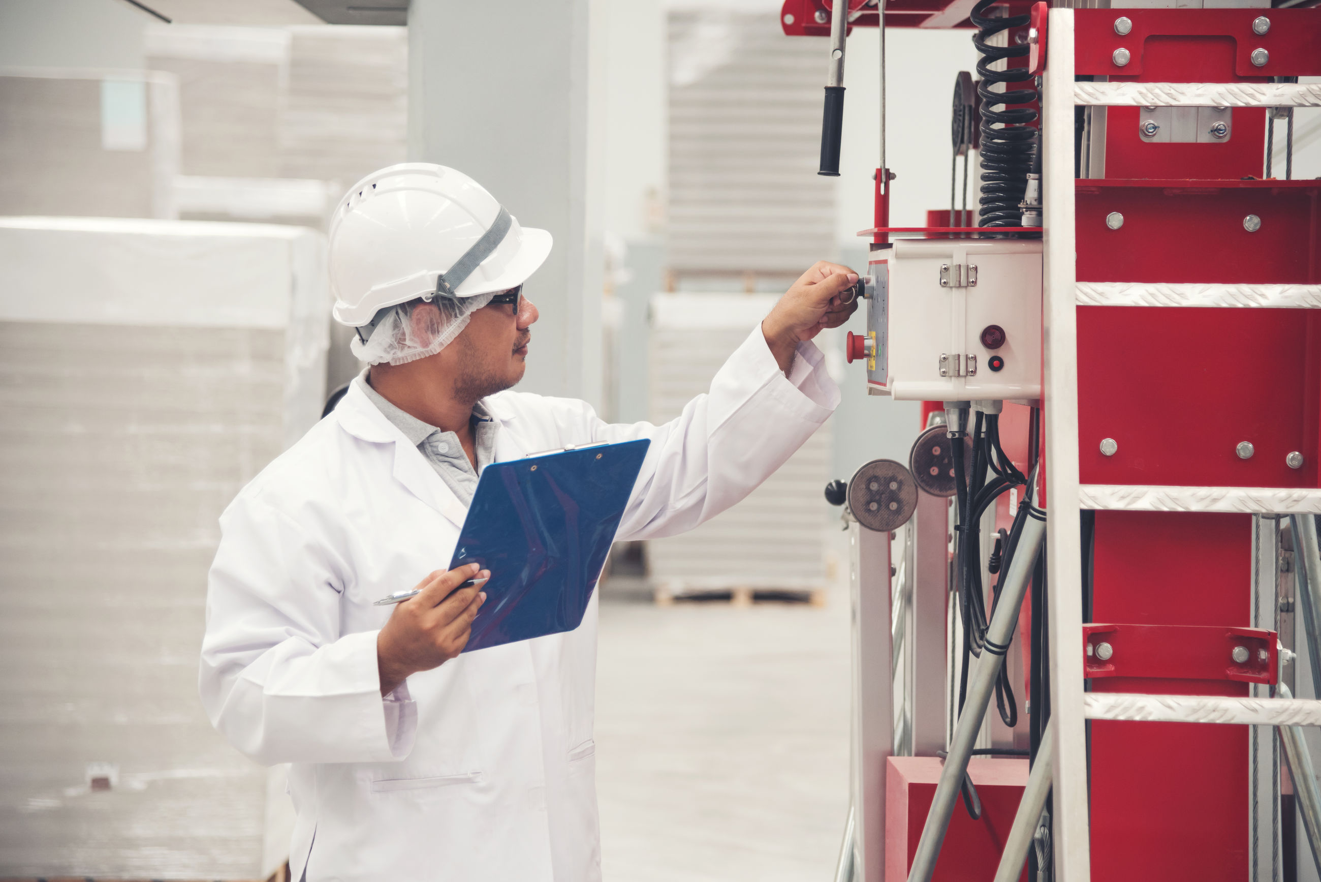 Male supervisor checking machinery at factory