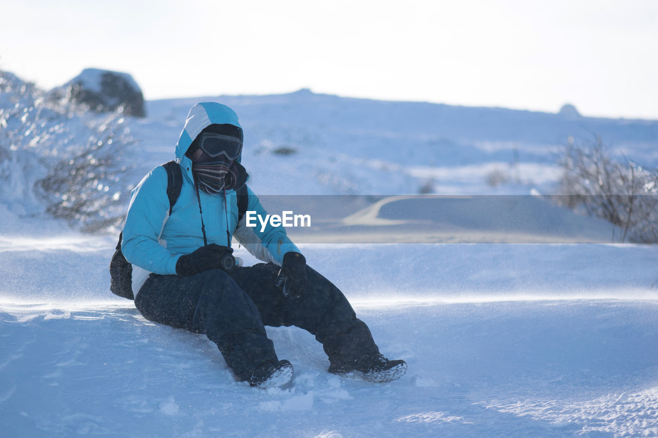 Full Length Of Person Sitting On Snow Covered Field Against Clear Sky