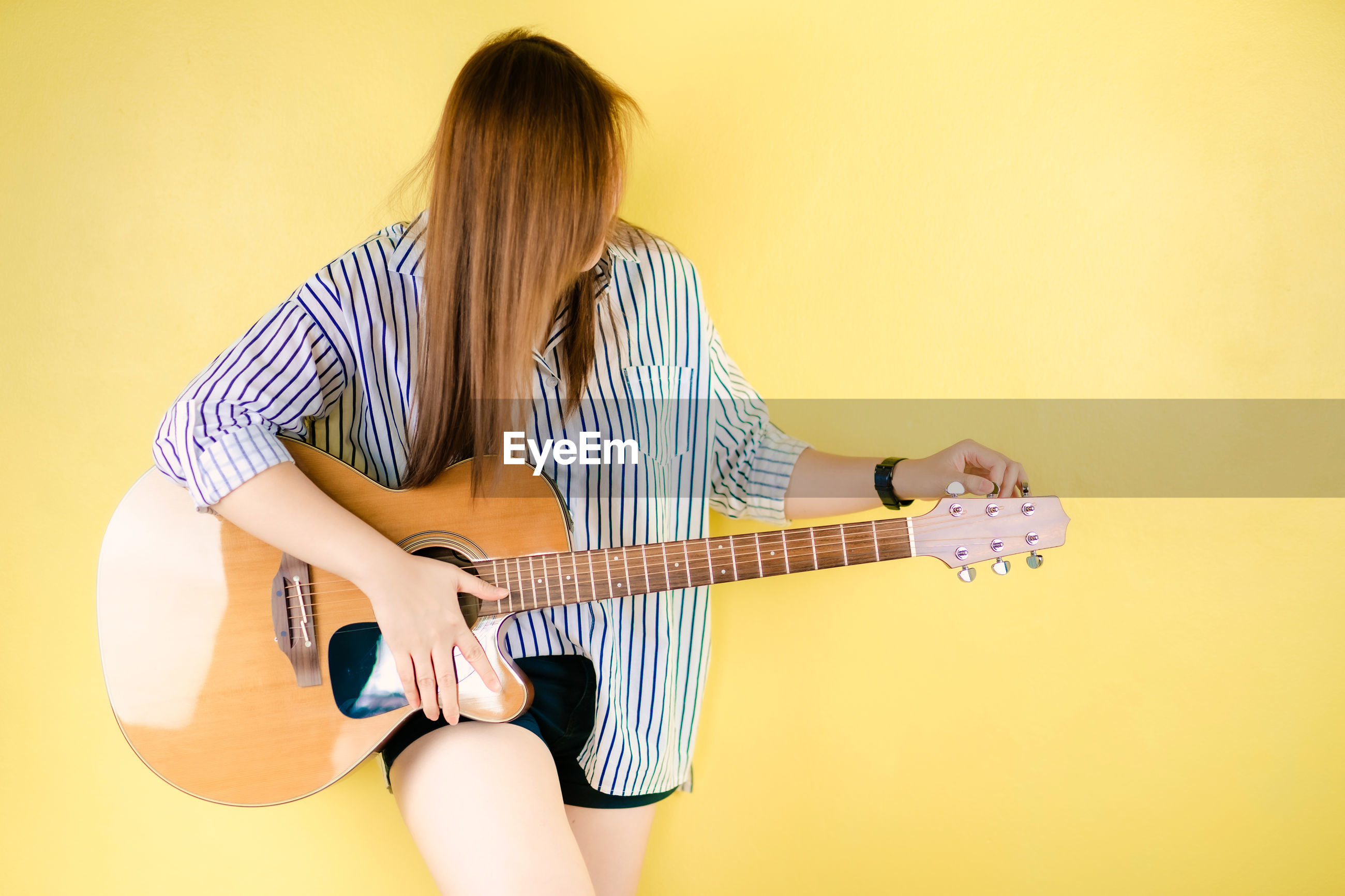 Woman playing guitar against wall
