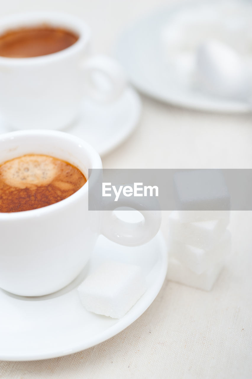 coffee cup, coffee - drink, food and drink, drink, refreshment, still life, saucer, cup, table, indoors, freshness, close-up, no people, sugar cube, frothy drink, sweet food, food, coffee bean, day