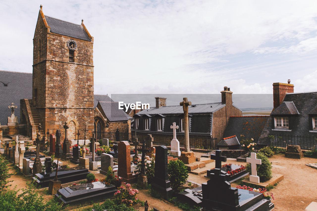 Cemetery By Church Against Cloudy Sky
