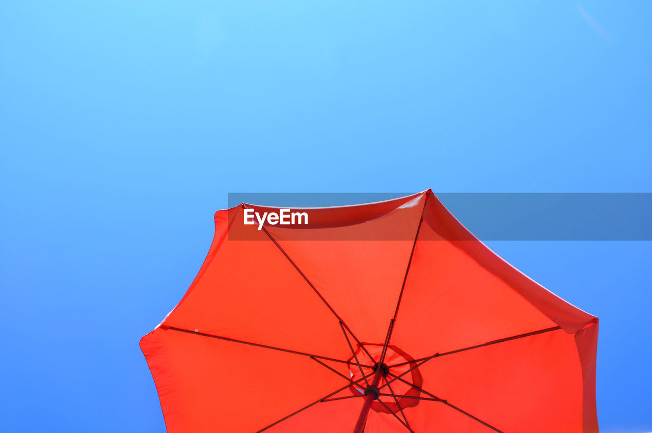 blue, copy space, sky, clear sky, low angle view, red, umbrella, protection, no people, security, nature, outdoors, close-up, pink color, single object, day, parasol, safety, studio shot, cut out, blue background