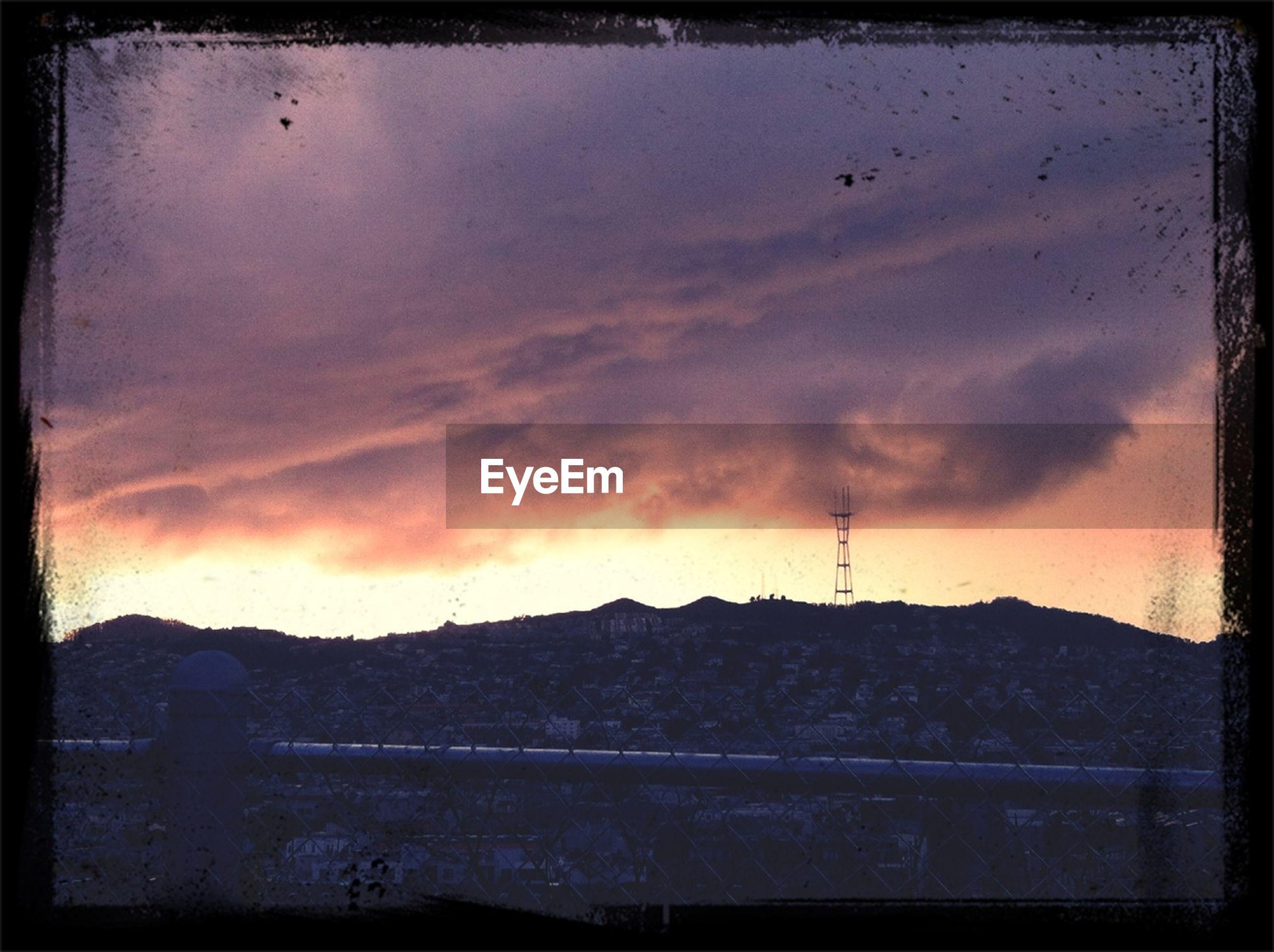 transfer print, auto post production filter, sky, sunset, silhouette, cloud - sky, cloudy, scenics, cloud, built structure, tranquility, building exterior, beauty in nature, dusk, orange color, tranquil scene, nature, outdoors, architecture, landscape