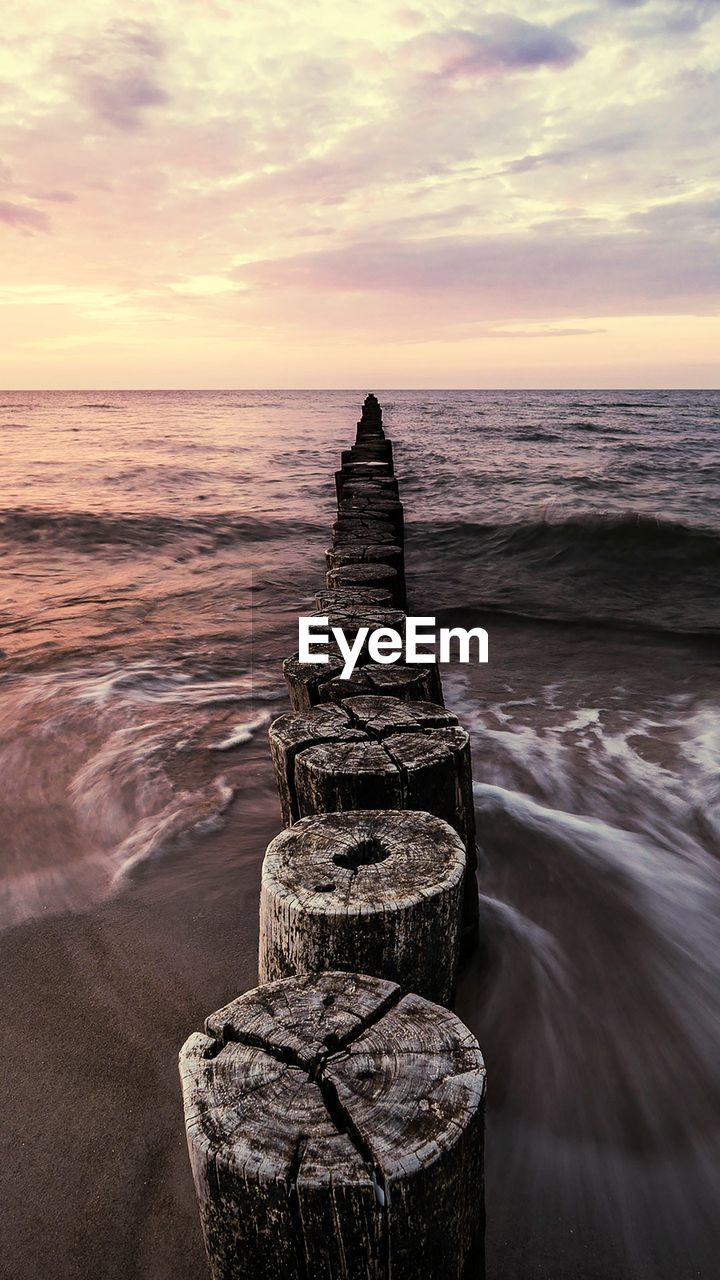 water, sea, sky, sunset, horizon, horizon over water, scenics - nature, beauty in nature, land, nature, tranquility, cloud - sky, motion, rock, beach, tranquil scene, solid, idyllic, no people, outdoors, wooden post, groyne