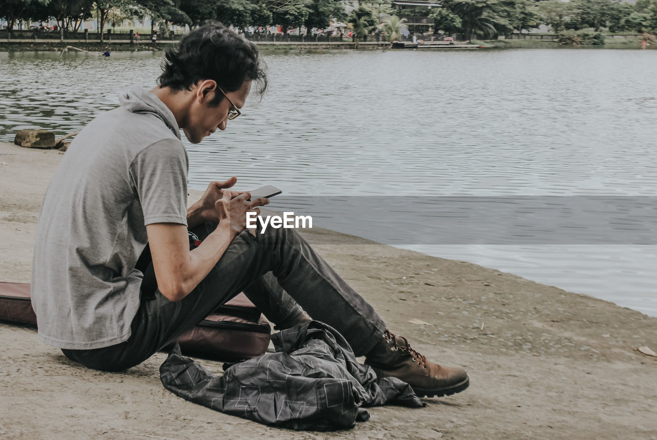 SIDE VIEW OF YOUNG MAN USING MOBILE PHONE AT RIVERBANK