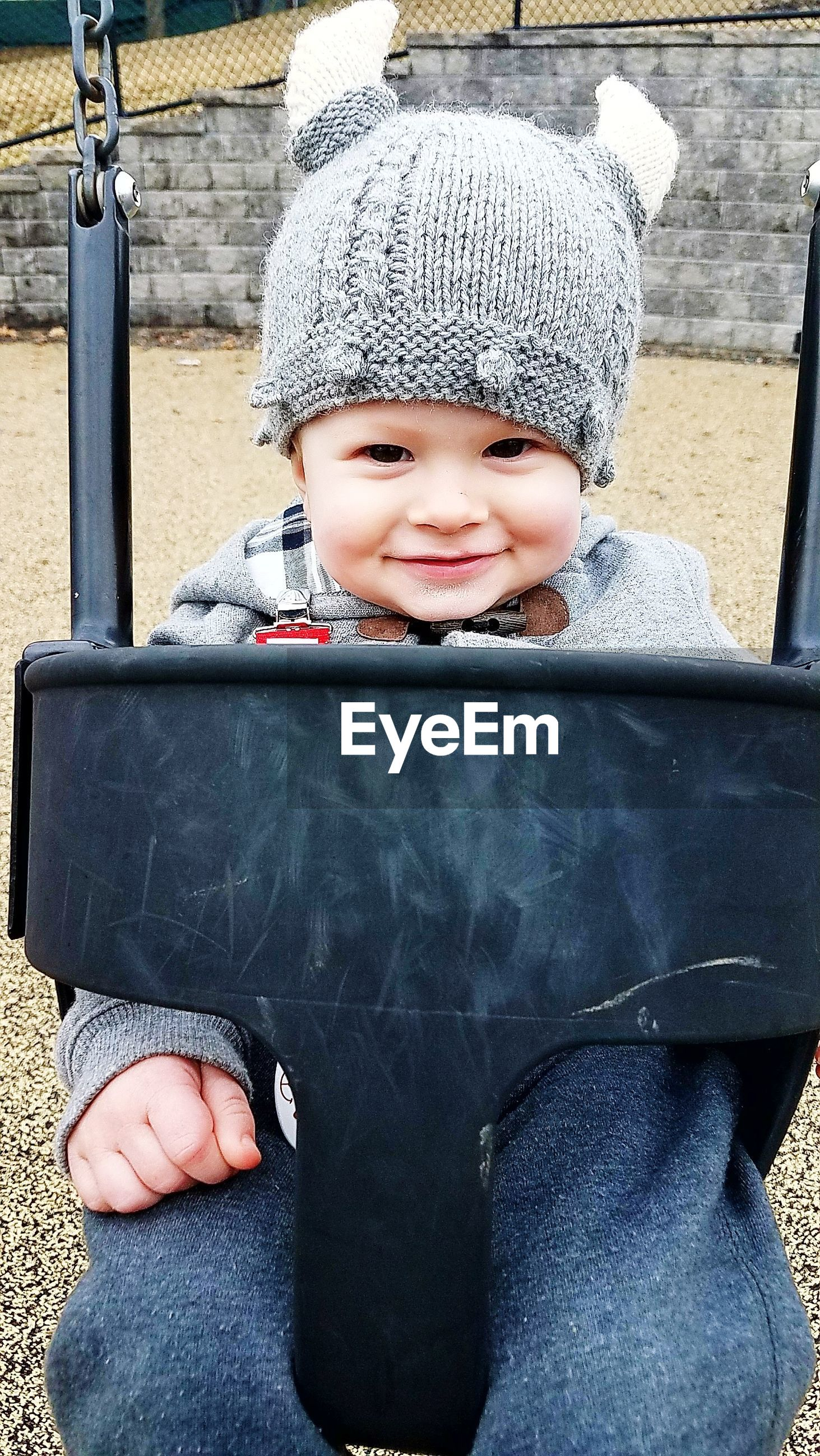 Portrait of cute smiling baby boy wearing warm clothing sitting on swing at playground